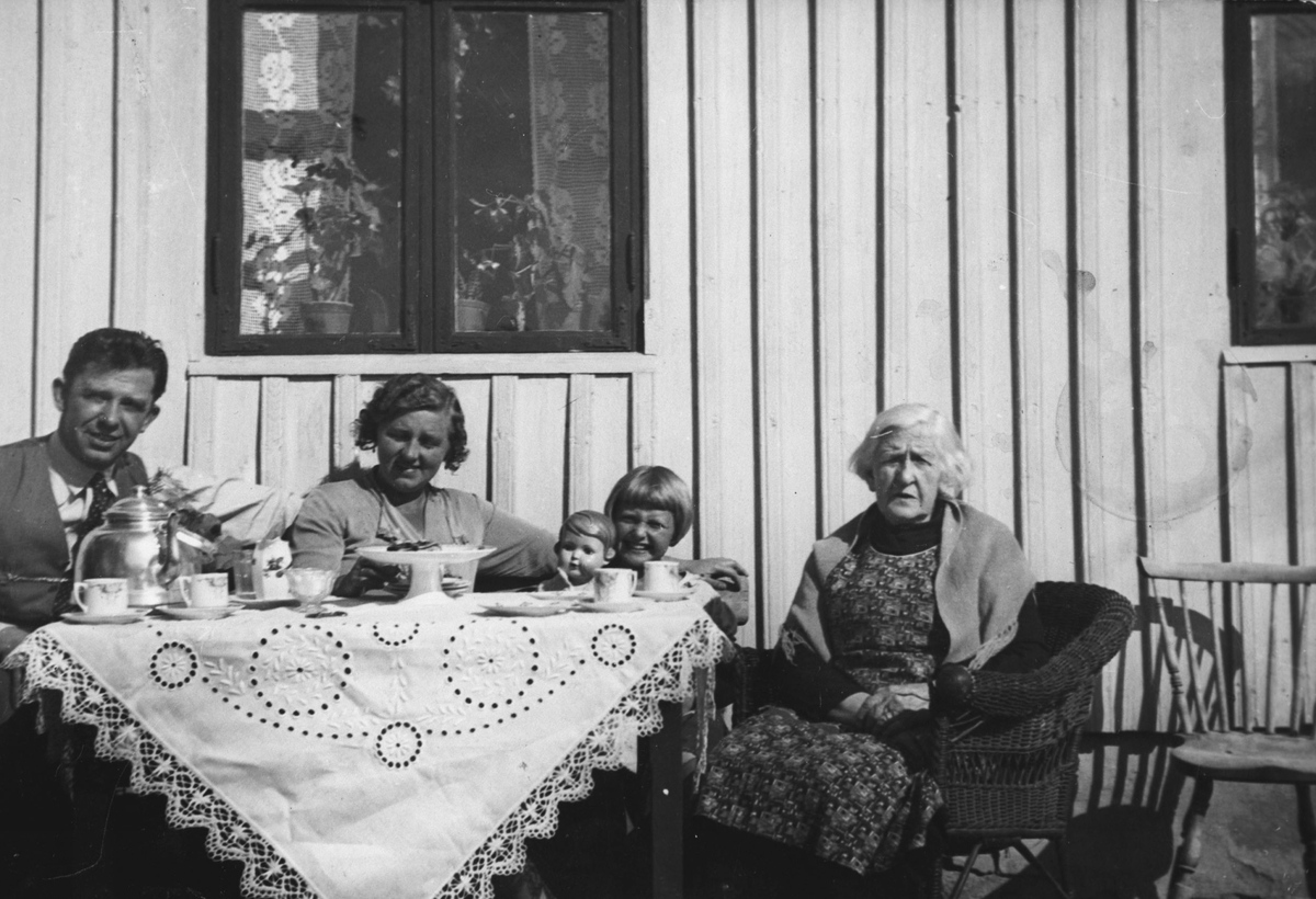 Erling, Solveig, Vesla og Helga Eriksen drikker kaffe ute i solveggen.