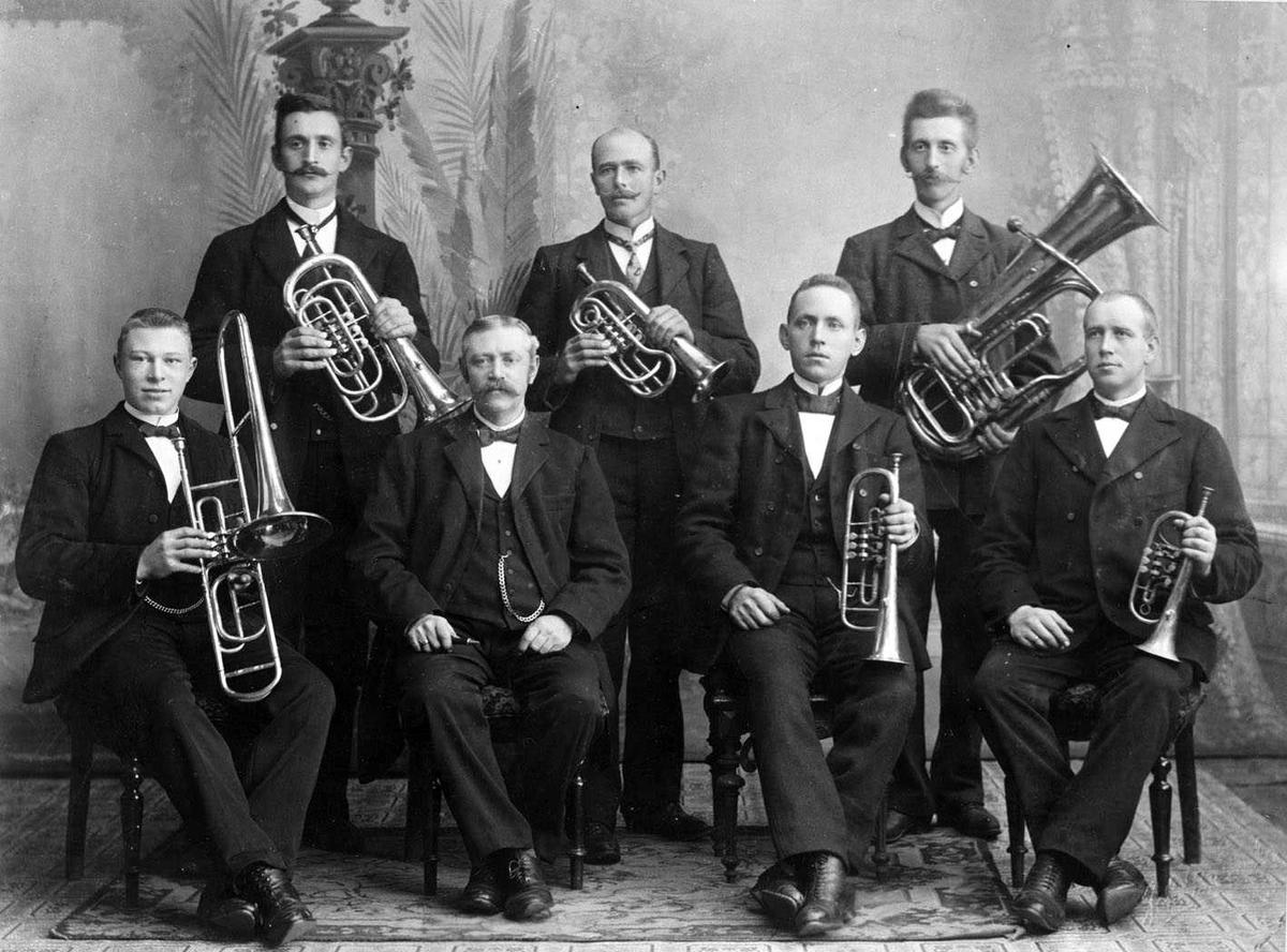Skedsmo musikken. 7 herrer med messinginstrumenter oppstilt for fotografering i studio