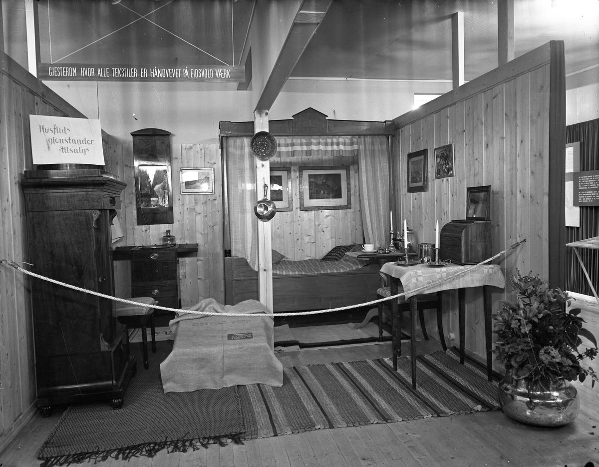 """Fra Eidsvoll Bygdeutstilling i 1955.  Husflidgjenstander fra Eidsvoll Verk, bl.a. """"Eidsvoldsduken""""."""