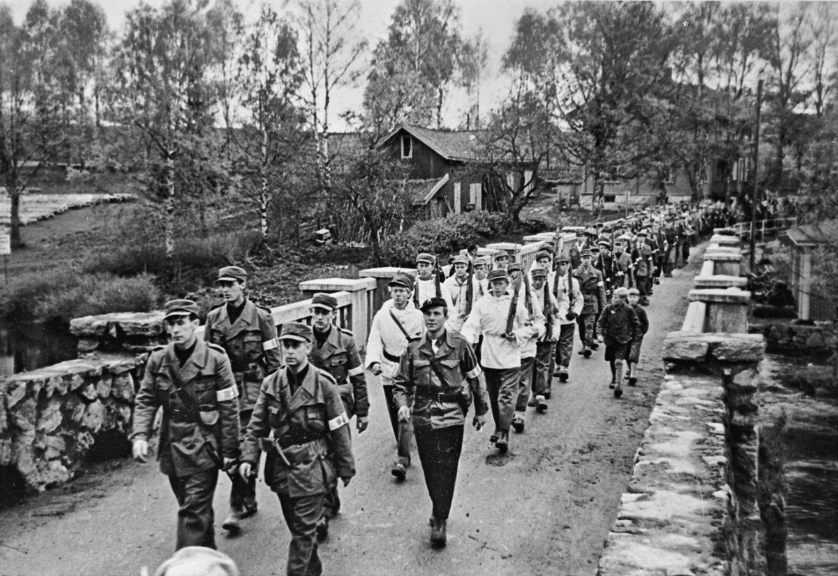 Hjemmestyrkene marsjerer over den gamle brua ved Eidsvollbygningen.