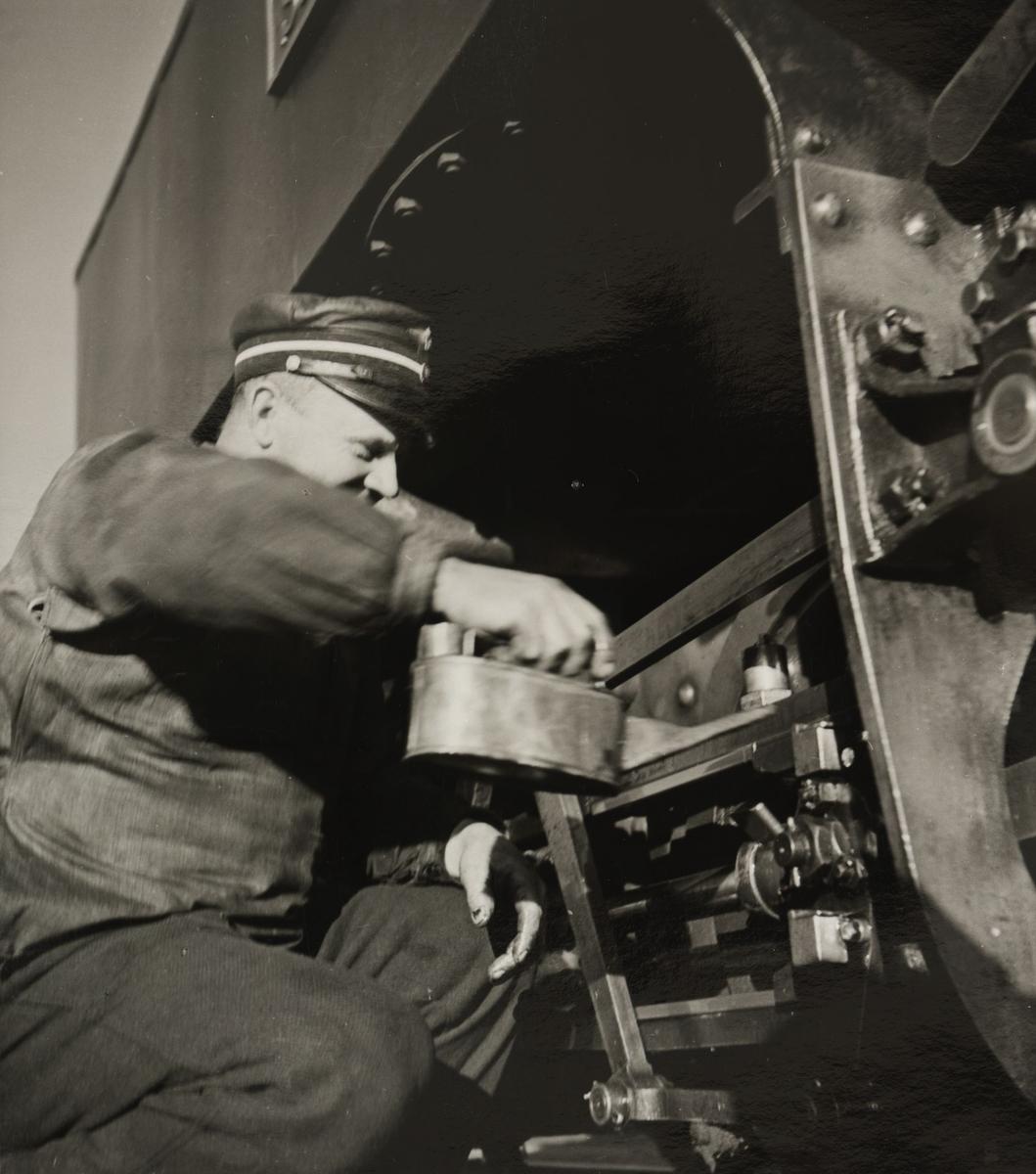 Lokomotivfører Syprian Aarstad smører gangtøyet på lokomotivet.