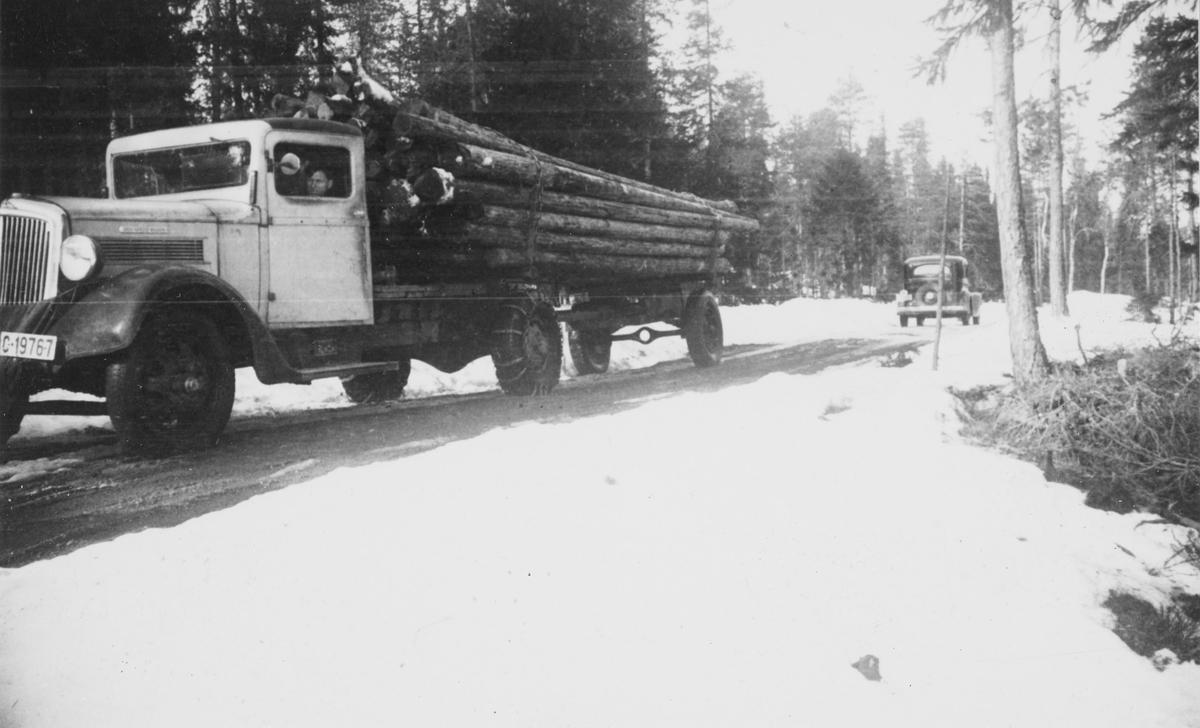 Tømmerbil underveis på dårlig vei i vårløsningen. Bilen er en 1936-modell Reo Speed Wagon.