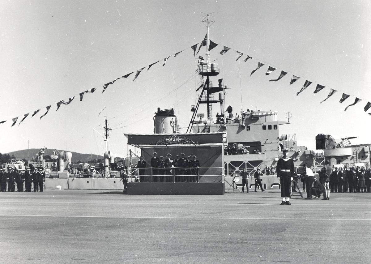 """Riverkl.- fregatt KNM """"Draug"""" ved kai i Haakonsvern under åpningen av basen 1963.  HM Kong Olav V  kan sees på podiet i midten av bildet."""