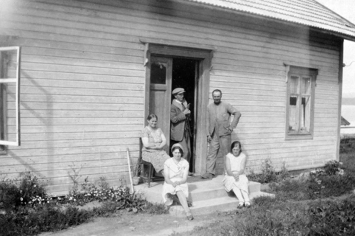 Ferjeekspedisjon og Helgøya Telefonselskap i Sundgård, Helgøya. På stolen sitter bestyrerinne ved Helgøen telefonsentral Helga Sund (1891-1962), til høyre er hennes mann bryggeekspeditør Karl Sund (1890-1962), de andre er Petter Røste f.1887, Ella og Emma Røste.