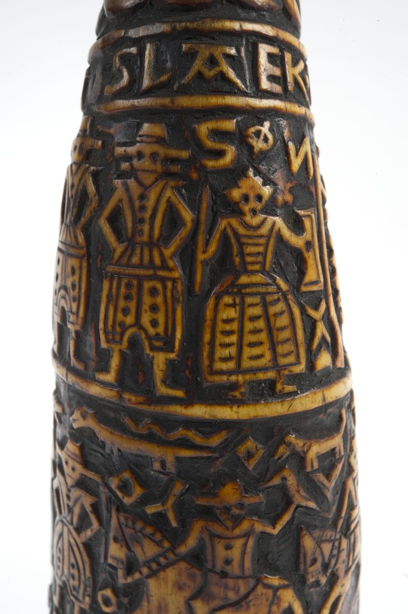 Krutthorn med flat bunnplate i tre med skåret ornamentikk. Ornamentikk på horn i form av menneskefigurer i fine drakter i to rekker, stående eller til hest, noen med våpen eller andre gjenstander i hendene. Forskjellige mindre dyr, bl. a. fugler, omgir menneskefigurene i nedre rekke.